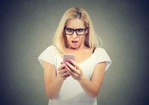 אישה מופתעת מסתכלת על טלפון נייד